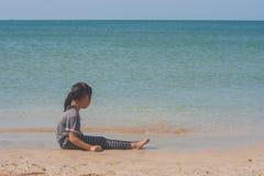Einsames nettes kleines Mädchen, das auf Sandstrand sitzt und zur Meerblickansicht schaut Stockfotos