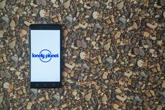Einsames Planetenlogo auf Smartphone auf Hintergrund von kleinen Steinen Lizenzfreies Stockfoto