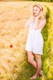 Einsames schönes junges blondes Mädchen im weißen Kleid mit Strohhut Stockbilder