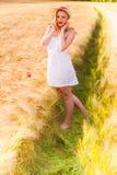 Einsames schönes junges blondes Mädchen im weißen Kleid mit Strohhut Stockbild