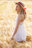 Einsames schönes junges blondes Mädchen im weißen Kleid mit Strohhut Lizenzfreie Stockfotos