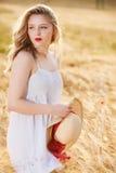 Einsames schönes junges blondes Mädchen im weißen Kleid mit Strohhut Stockfoto