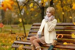 Einsames schönes Mädchen, das im Herbstpark auf der Holzbank sitzt Lizenzfreies Stockfoto