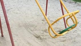 Einsames Schwingen wie Symboleinsamkeit und -bohren Leeres Spielplatzschwingen des Solitariness auf Sand Extreem-Zeitlupefarbe stock footage