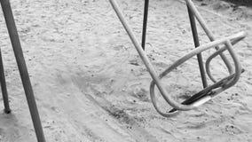Einsames Schwingen wie Symboleinsamkeit und -bohren Leeres Spielplatzschwingen des Solitariness auf Sand Extreem-Zeitlupeschwarze stock footage