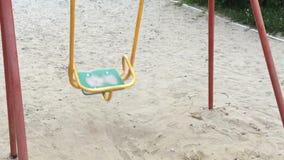 Einsames Schwingen wie Symboleinsamkeit und -bohren Leeres Spielplatzschwingen des Solitariness auf Sand Langsame Bewegung stock video footage