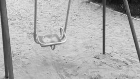 Einsames Schwingen wie Symboleinsamkeit und -bohren Leeres Spielplatzschwingen des Solitariness auf Sand Zeitlupe Schwarzweiss stock footage