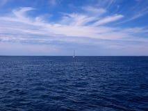 Einsames Segelboot auf dem Ozean Stockbild