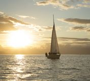Einsames Segelboot bei Sonnenuntergang stockfoto