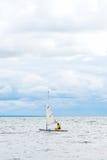 Einsames Segelboot im Meer, im bewölkten Himmel und im Silber-Wasser Lizenzfreie Stockfotos