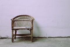 Einsames Stillstehen des alten Stuhls vor Betonmauer Lizenzfreies Stockbild
