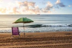 Einsames sunbed mit Regenschirm auf der Küste Stockfoto