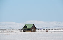 Einsames traditionelles isländisches Haus umgeben durch Schneelandschaft stockbilder