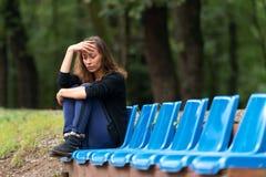 einsames, unglückliches, trauriges Mädchen, das auf dem Fußboden in einem dunklen schmutzigen Eckraum sitzt Lizenzfreie Stockfotos