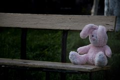 Einsames vergessenes verlassenes Teddybärspielzeughäschen saß auf einer alten Holzbank und einem Warteinhaber lizenzfreie stockfotografie