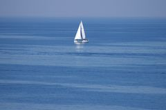 Einsames weißes Segel in endlosem Ozean Stockfoto