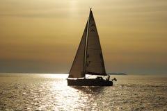 ?Einsames weißes Segel in endlosem Ozean auf einem Sonnenuntergang Lizenzfreie Stockfotografie