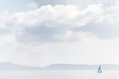 Einsames Yachtsegeln auf einem ruhigen See Lizenzfreie Stockbilder