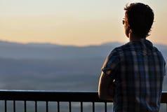 Einsamkeit - junger Mann, der über Bergen anstarrt lizenzfreies stockfoto