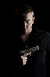 Einschüchternder Mann, der eine Gewehr zu seinem Kasten anhält Stockfotos