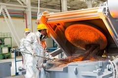 Einschmelzen in einer metallurgischen Anlage Flüssiges Metallfleck Stockfotos