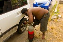 Einsetzen der Luft in ein Rad auf eine karibische Insel Lizenzfreie Stockfotografie