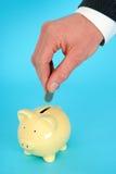 Einsetzen des Geldes in eine piggy Querneigung Lizenzfreie Stockbilder