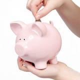 Einsetzen des Geldes in Sparschwein Stockbilder