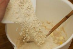 Einsetzen des Mehls in eine Schüssel Lizenzfreie Stockfotografie