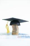 Einsparung für Hochschulausbildung mit Doktorhut auf einem Stapel Euromünzen und Banknoten Stockfotografie