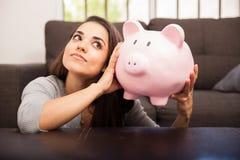Einsparung-Geld in einer Piggy Querneigung stockfotos