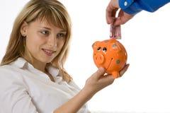 Einsparung-Geld in einer Piggy Querneigung Lizenzfreie Stockfotos