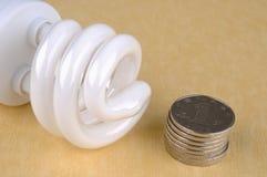 Einsparungelektrizitätslampe und -münzen Stockfotografie