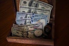 Einsparungen in den Dollar gespeichert in der alten Holzkiste mit alter Uhr und s Lizenzfreie Stockfotografie
