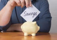 Einsparungen in einen Geldkasten stockbild