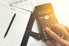 Einsparungen, Finanzen, Wirtschaft und Bürokonzept - nah oben vom Mann mit dem Taschenrechner, der Anmerkungen machend zählt Stockfoto
