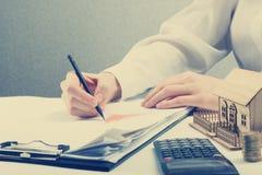 Einsparungen, Finanzen, Wirtschaft und Hauptbudgetkonzept - nah oben von der Frau, die bei Taschenrechnerverlusten, Gewinn bringe Lizenzfreie Stockbilder