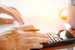 Einsparungen, Finanzen, Wirtschaft und Hauptkonzept - nah oben vom Mann mit dem Taschenrechner, der Anmerkungen zu Hause machend  Stockbild