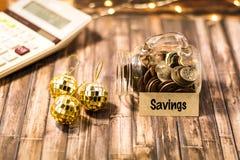 Einsparungensgeld-Glas-Motivkonzept auf hölzernem Brett Stockfoto