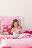 Einsparunggeld des kleinen Mädchens in einer Piggyquerneigung Lizenzfreie Stockfotografie