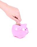 Einsparunggeld, Hand setzt Münze in piggy Querneigung Lizenzfreies Stockfoto