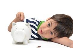 Einsparungsgeld des kleinen Jungen lizenzfreie stockfotos