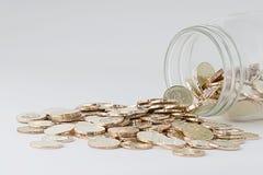 Einsparungskonzept-Goldmünzen mit einer Flasche Stockfoto