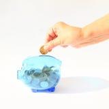 Einsparungsschwein in der Hand gefüllt mit Münze Lizenzfreies Stockbild