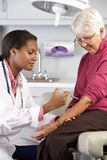 Einspritzung Doktor-Giving Senior Female Patient Stockbild