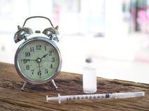Einspritzungen, Flaschen, Pillen und Uhren bedeuten, dass Zeit für Einspritzung für Diabetiker Insulineinspritzungen erfordert lizenzfreie stockbilder