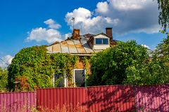 Einstöckiges Haus des alten Ziegelsteines überwältigt mit gelockter Virginia-Kriechpflanze stockfotos