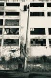 Einstürzender konkreter Laternenpfahl vor dem Zerbröckeln des Industriegebäudes Stockbilder