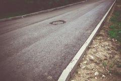 Einsteigeloch auf der Straße Stockfotografie