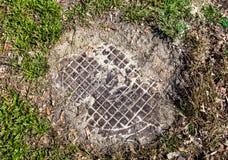 Einsteigeloch mit der Metallabdeckung gesunken in den Boden und in das Gras Stockfotos